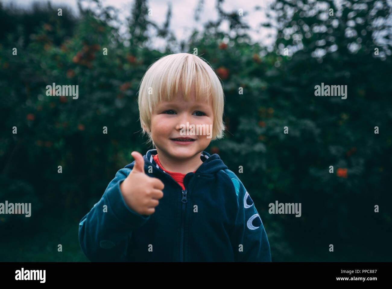 Lächelnde Junge Blonde Haare Braune Augen Daumen Hoch Stockfoto
