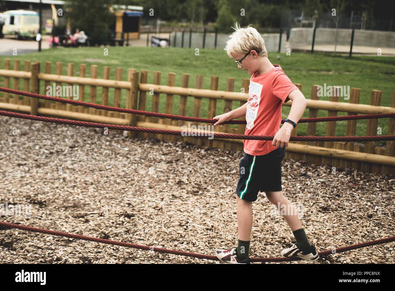 Blonde Junge spielt auf einem Spiel Park Stockbild