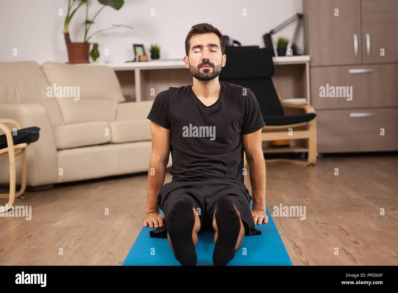 Fußboden Ideen Yoga ~ Junger mann sitzen auf dem boden tun paschimottanasana yoga dar