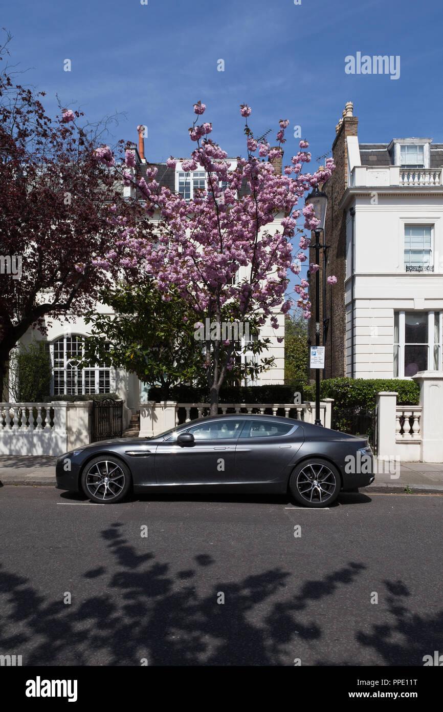 Aston Martin vor teuren Häuser mit Bäume in Blüte geparkt. Stockbild