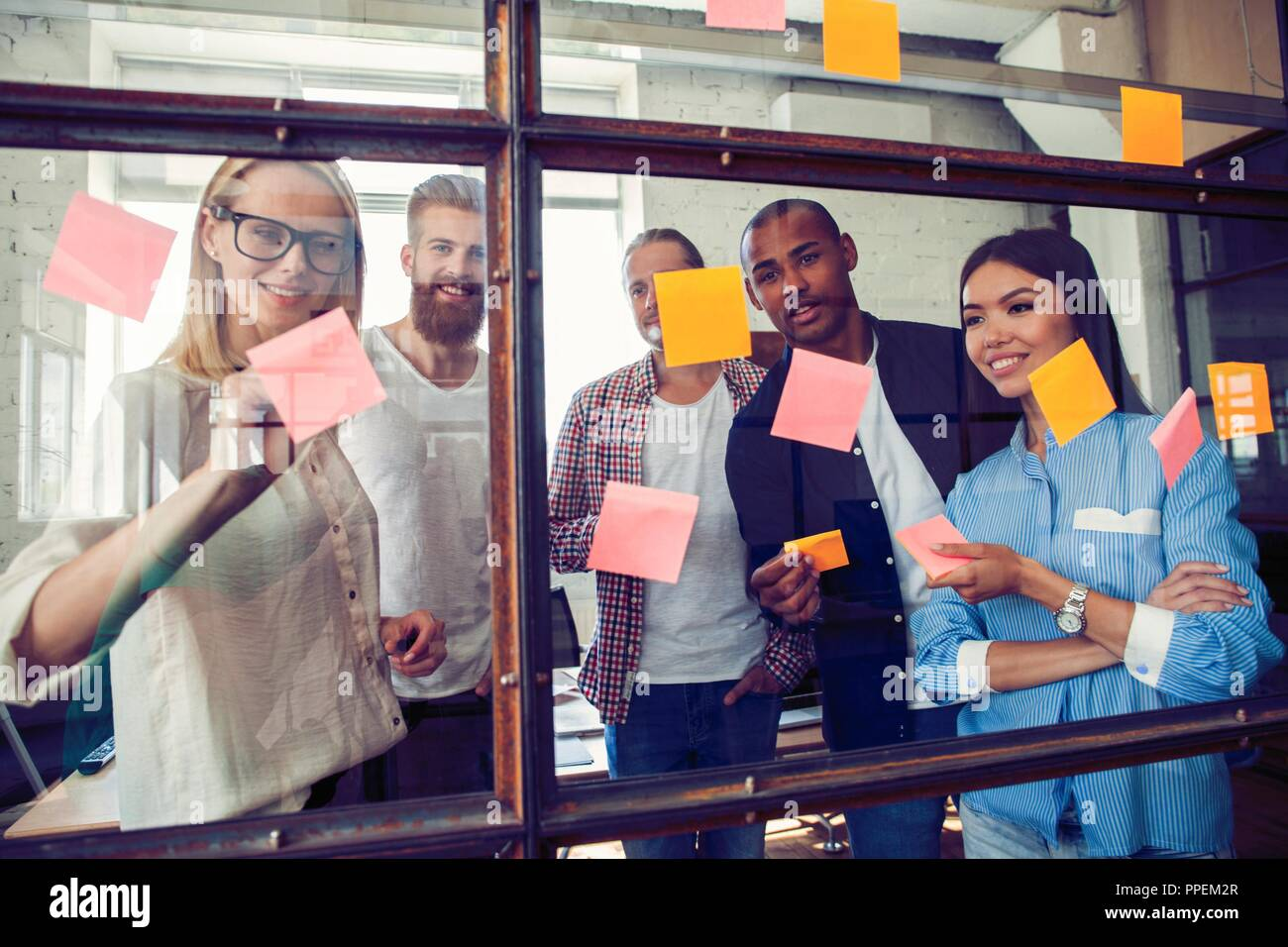 Business Leute, die im Büro und Post-it Notizen Idee zu teilen. Brainstorming Konzept. Haftnotiz auf Glas Wand Stockbild