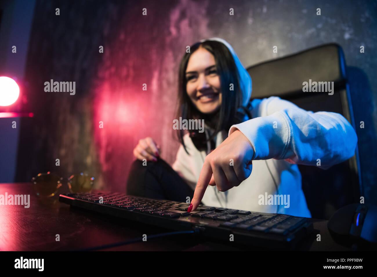 Frau in der Haube sitzen und Arbeiten am Laptop als Hacker. Ausführen von malware Programm auf Rechner im Internet mit boshaften Lächeln auf ihrem Gesicht. Stockbild