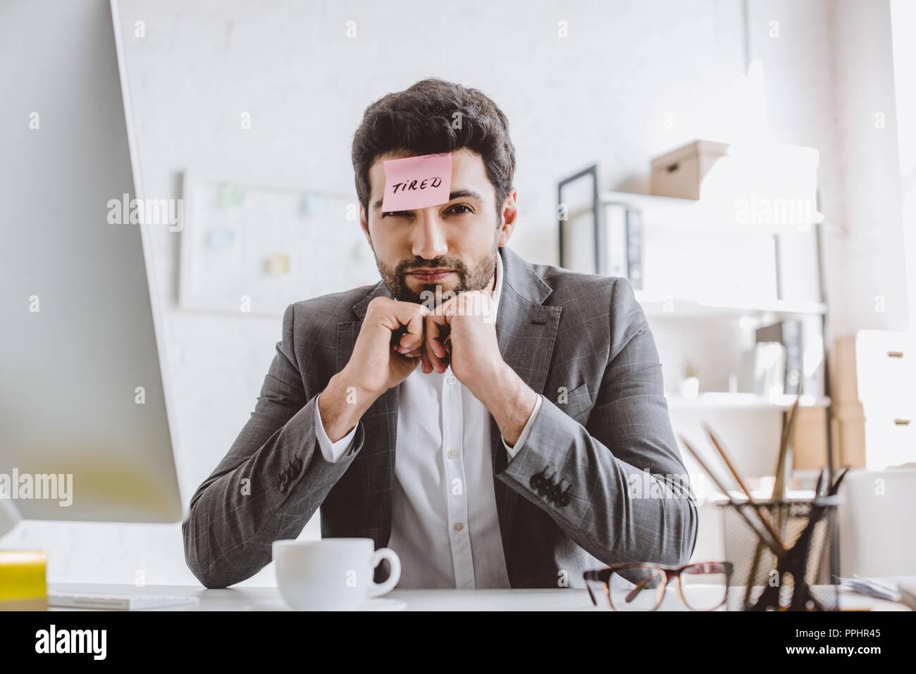 Geschäftsmann mit einem Aufkleber auf der Stirn mit Word im Büro müde Stockbild