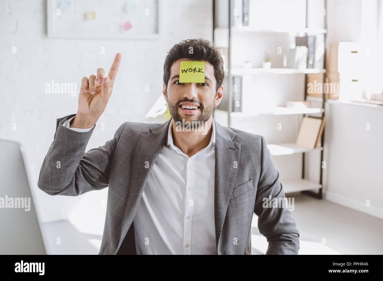 Fröhliche Geschäftsmann nach oben zeigt, und sitzen mit einem Aufkleber auf der Stirn mit Word arbeiten im Büro Stockbild