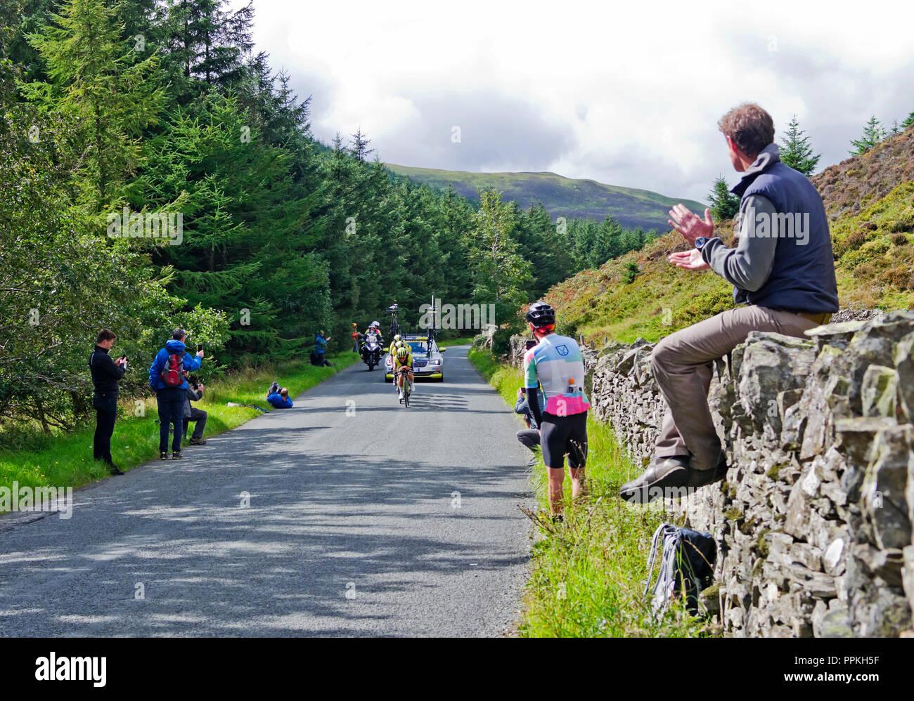 Stufe 5 Tour durch Großbritannien 2018. Zuschauer sitzen auf dem trockenen Steinmauer begrüßt Ankunft von Michelton Scott im Mannschaftszeitfahren, Whinlatter Pass, Cumbria. Stockbild