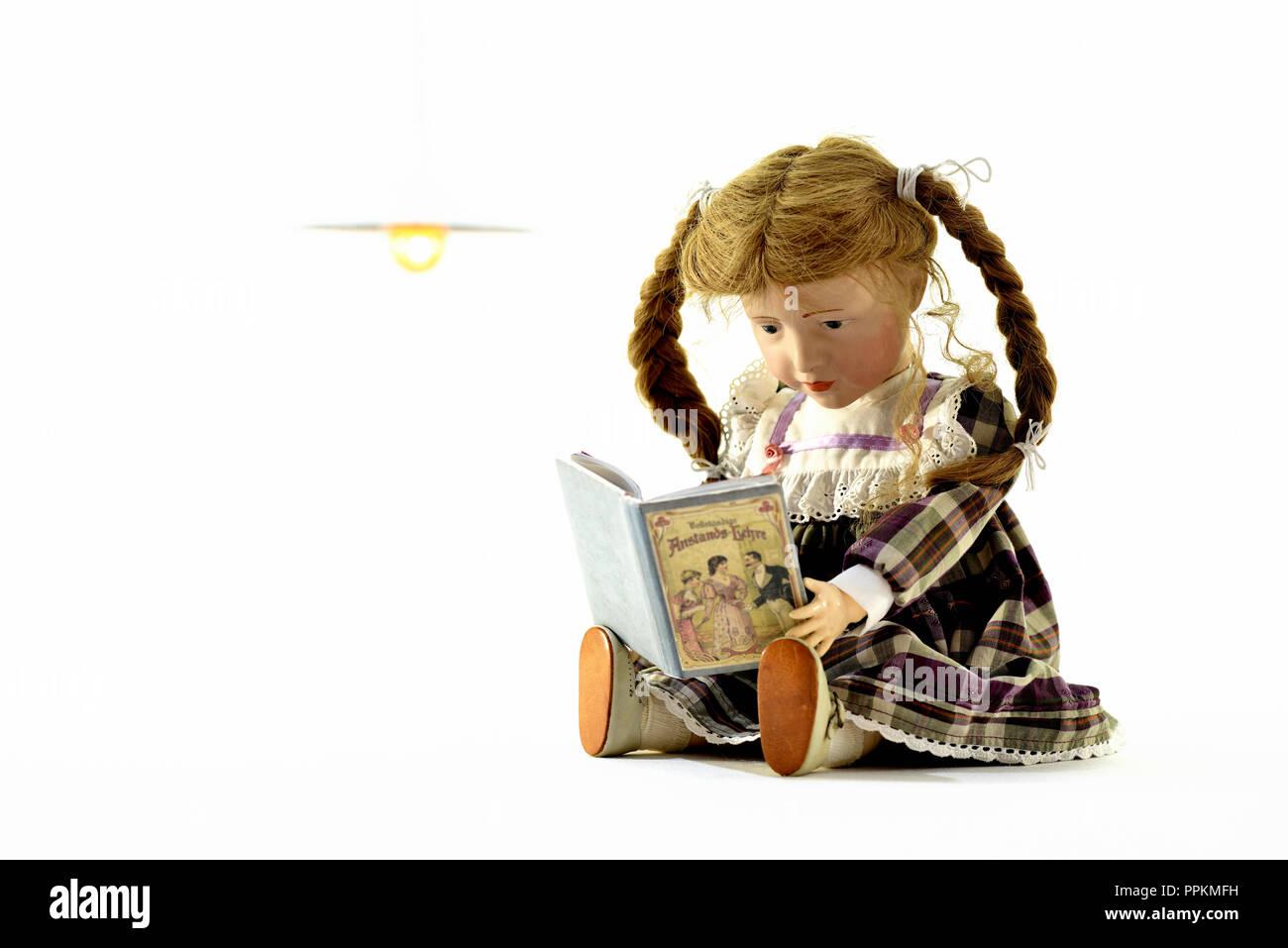 Puppe Elise (Kopf 109 von Kaemmer & Reinhardt, Jahr 1909) liest ein Buch ueber Anstands-Lehre (Puppe Elise sitzt und liest ein Buch über Anstand) Stockfoto