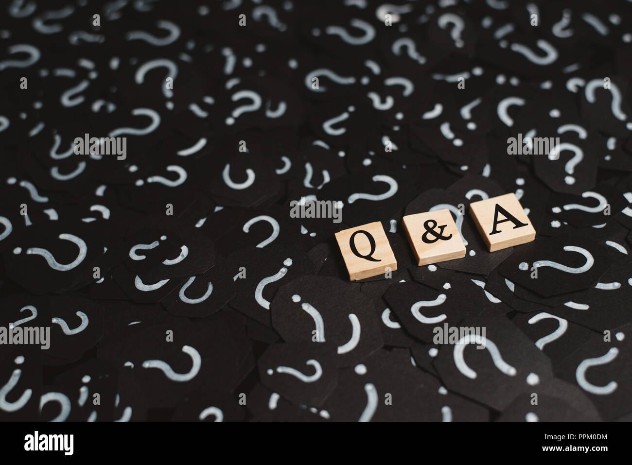 Alphabet aus Holz Fliesen mit Q&A Buchstaben auf schwarzem Papier mit Fragezeichen. Konzept von Frage und Antwort Q&A online unterstützen. Stockbild