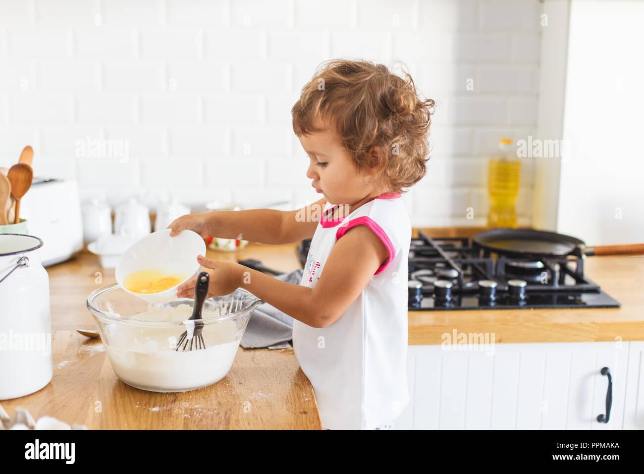 Kleines Mädchen Zubereitung Teig für Pfannkuchen in der Küche. Konzept der Lebensmittelzubereitung, weiße Küche für den Hintergrund. Casual Lifestyle Foto serie in re Stockbild