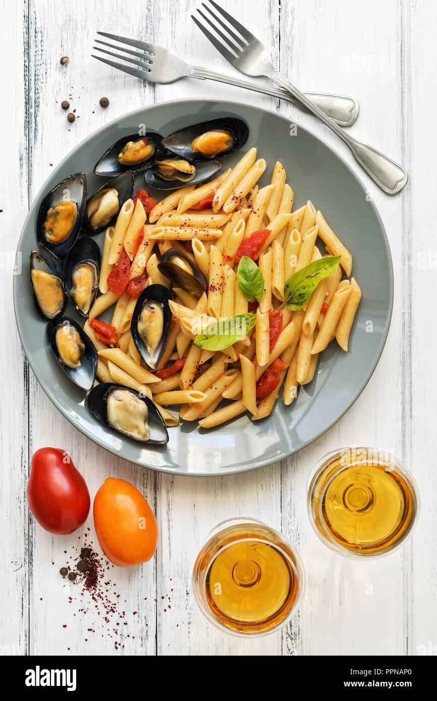 Penne Pasta mit Miesmuscheln, Tomaten und Wein auf einem weißen Holzmöbeln rustikal Hintergrund. Ansicht von oben, flach. Mediterrane Küche Stockbild