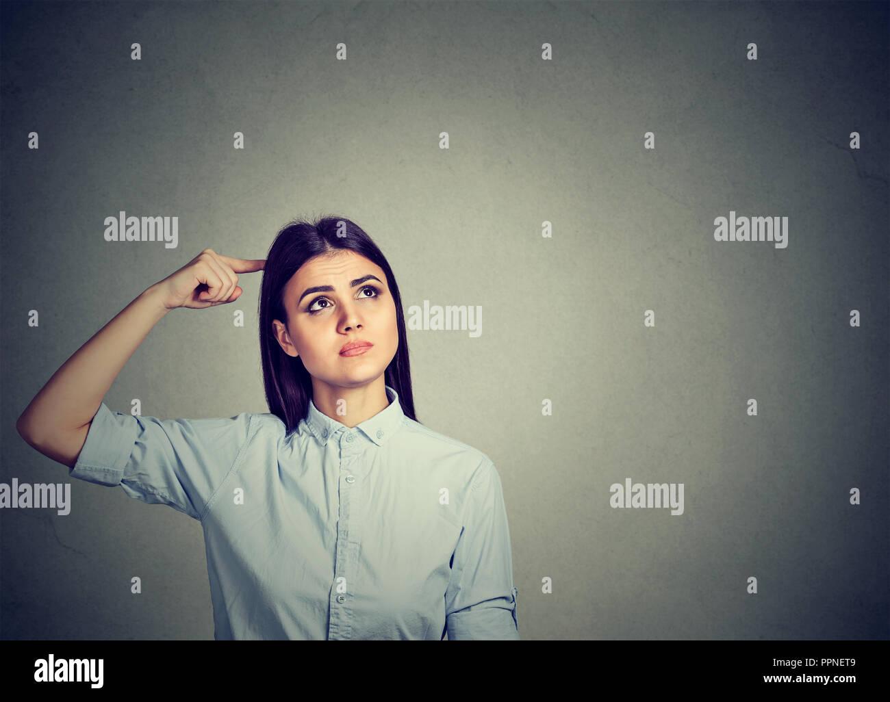 Junge verwirrte brünette Frau kratzen Kopf in perplexion weg schauen Stockbild