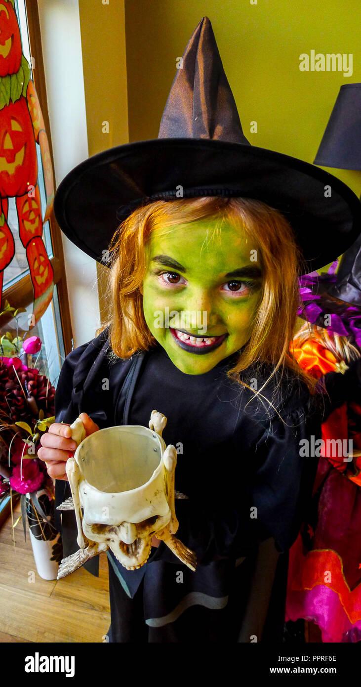 Halloween Gesichter Hexe.Madchen Mit Einem Grunen Gesicht Gesicht Farbe In Einem Kid Halloween Hexe Kostum Gekleidet Tragt Einen Schwarzen Hexen Hut Und Schwarzen Kleid Stockfotografie Alamy