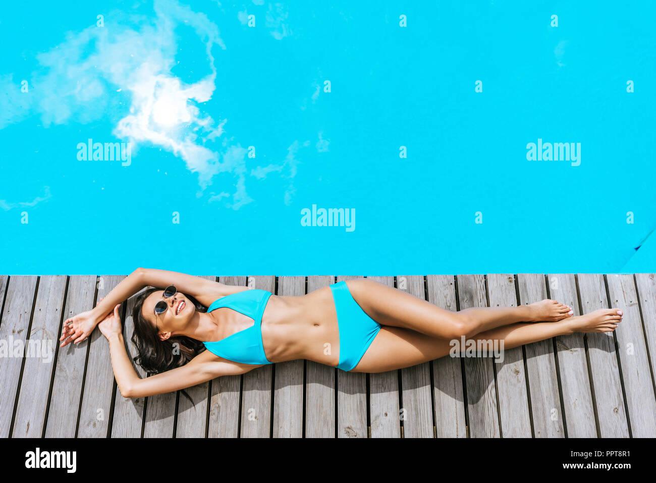 Blick von oben auf die schönen Lächeln brünette Frau im Bikini und Sonnenbrille ruht in der Nähe von Pool Stockbild