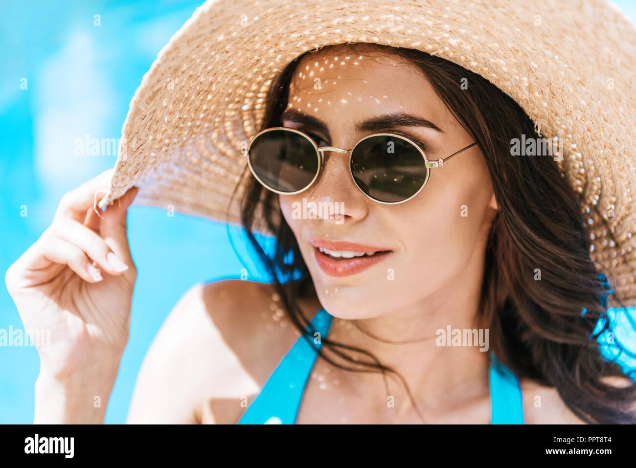 Schöne brünette Frau mit Sonnenbrille und Strohhut am Pool lächelnd Stockbild