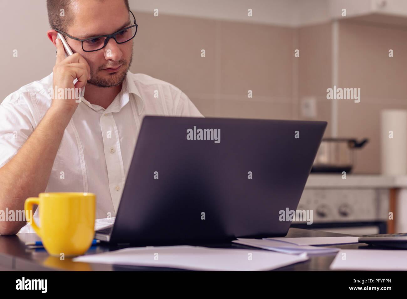 Junge kreative Menschen arbeiten mit Computer, während am Telefon sprechen zu Hause Stockfoto