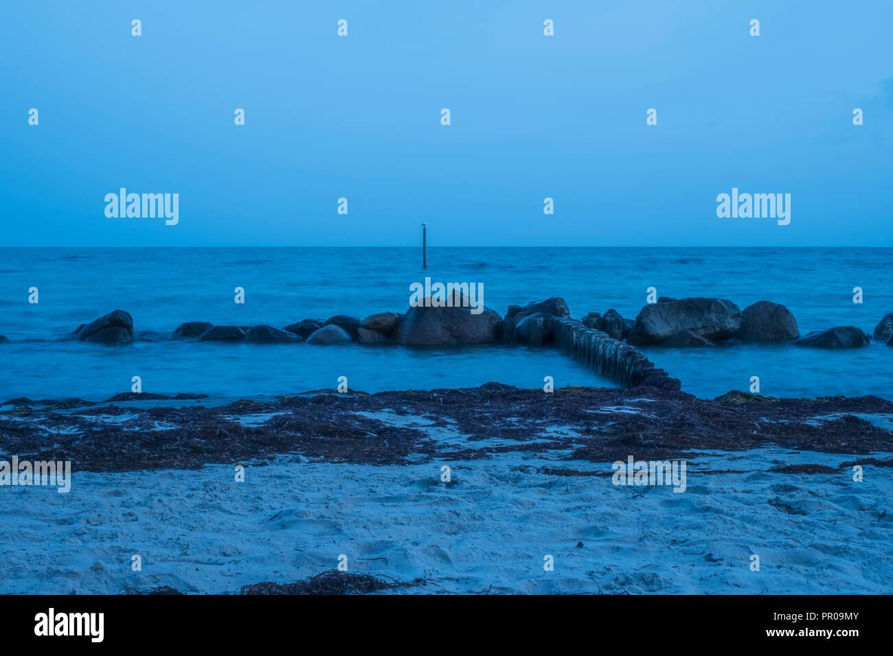 Felsen am Ufer in bläuliche milchiges Wasser nach Sonnenuntergang während der Blauen Stunde bei Rabylille Strand, Insel Mön, Dänemark, Skandinavien, Europa. Stockbild