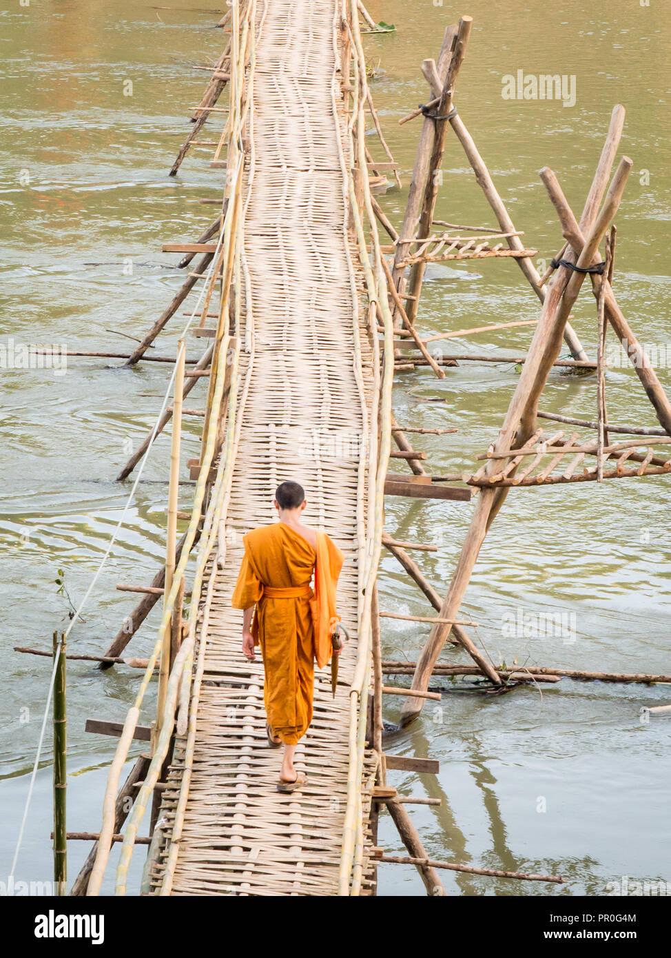Orange gekleideten buddhistischen Mönch beim Überqueren einer Brücke aus Bambus, Luang Prabang, Laos, Indochina, Südostasien, Asien Stockbild