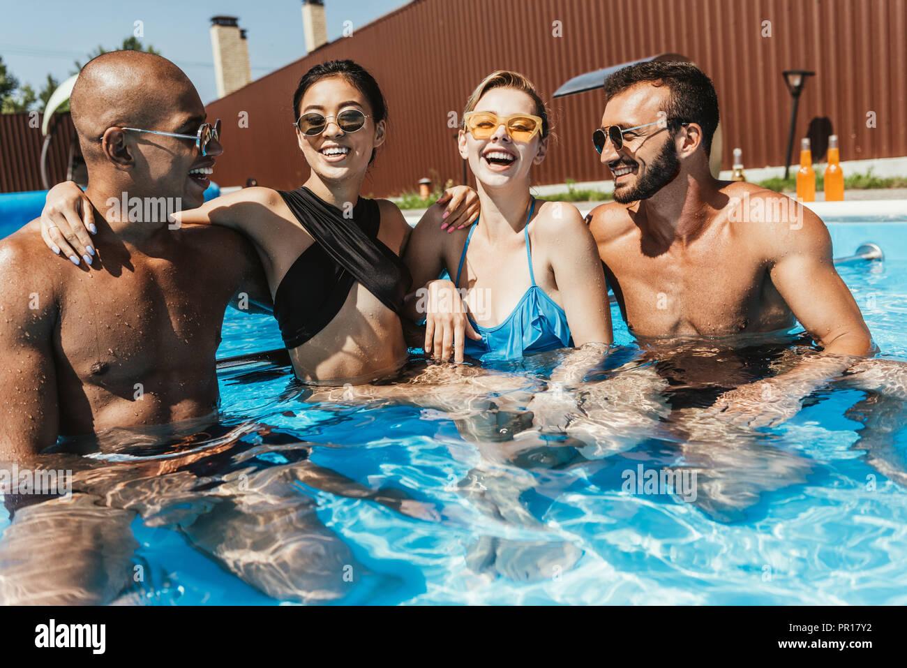 Lachend multiethnischen Paare in Sonnenbrille Zeit im Pool Stockbild