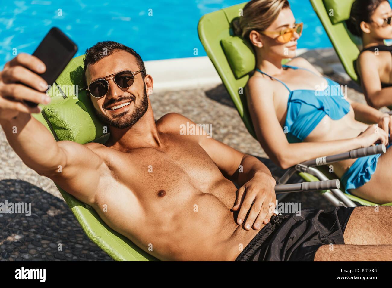 Mann unter selfie mit Mädchen beim Sonnenbaden auf Sonnenliegen am Pool Stockbild