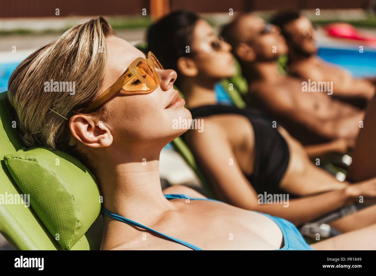 Multiethnischen Freunde in Sonnenbrille Sonnenbaden auf Sonnenliegen am Pool, selektiver Fokus Stockbild