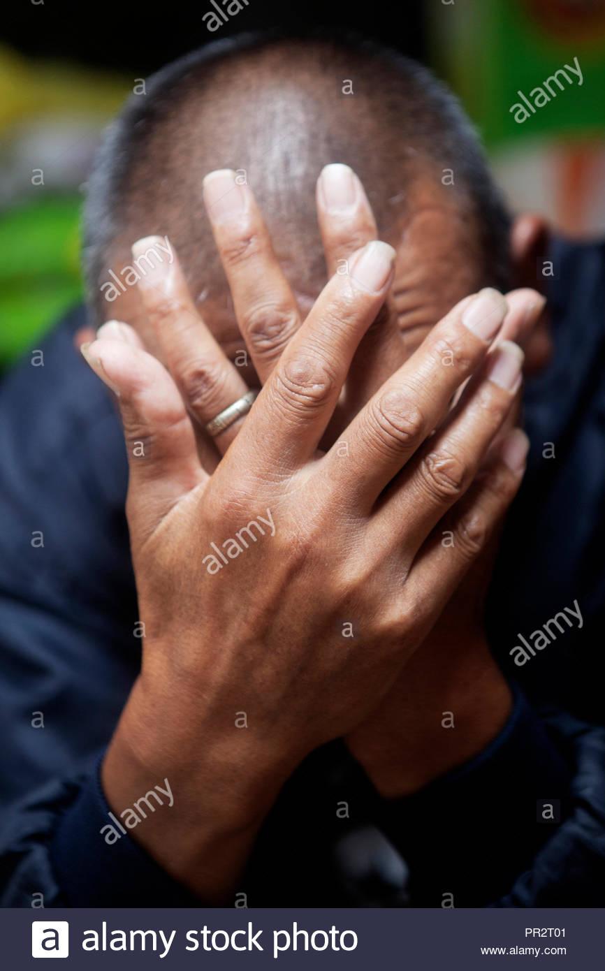 Die Hände, das Gesicht eines traurigen Menschen. Stockbild