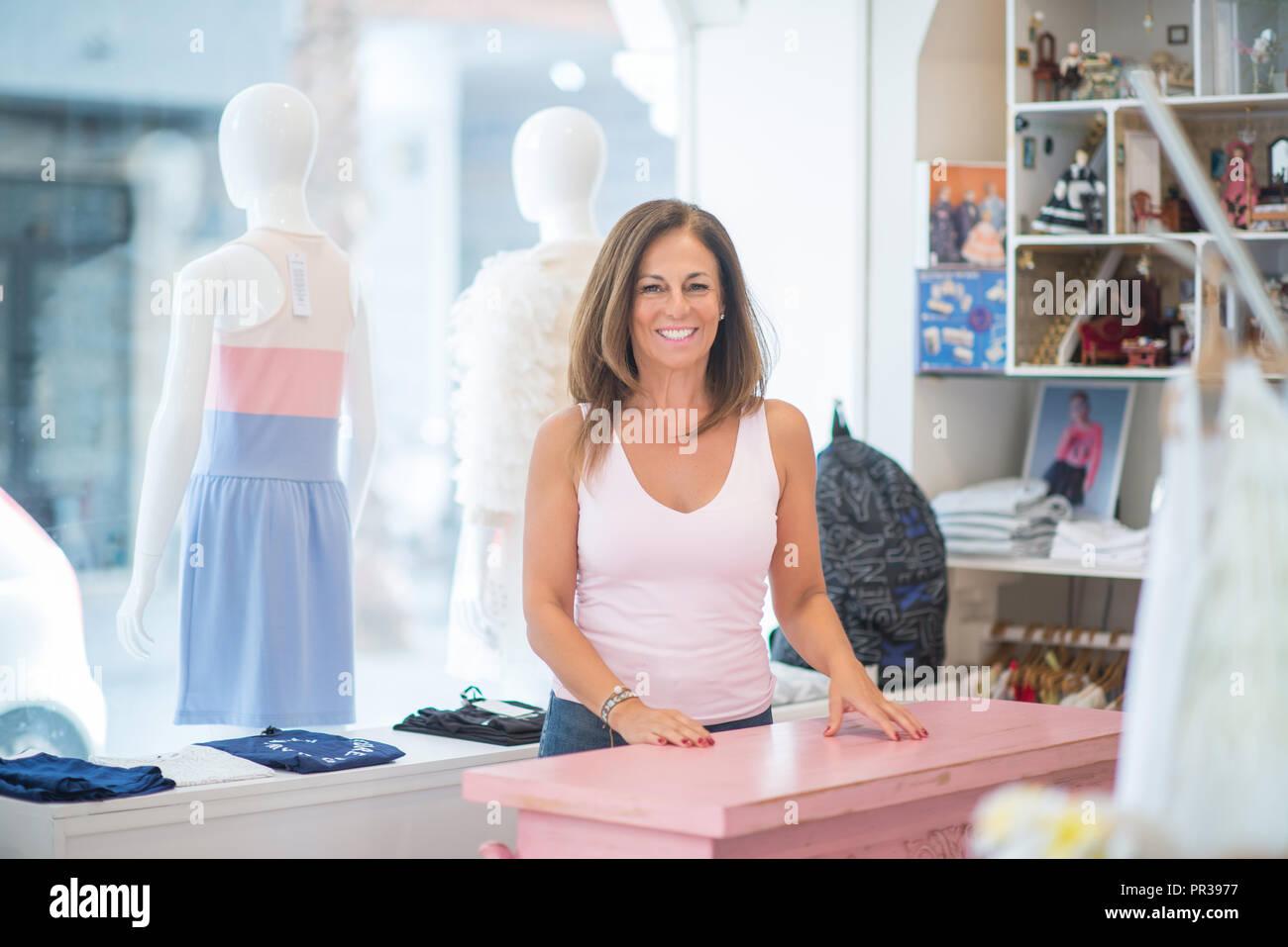 308e424dadfc82 Schönen mittleren Alter spanischer stehende Frau mit einem Lächeln auf dem  Gesicht an Kleidung zu speichern. Shop Besitzer und Verkäufer lächelt ...