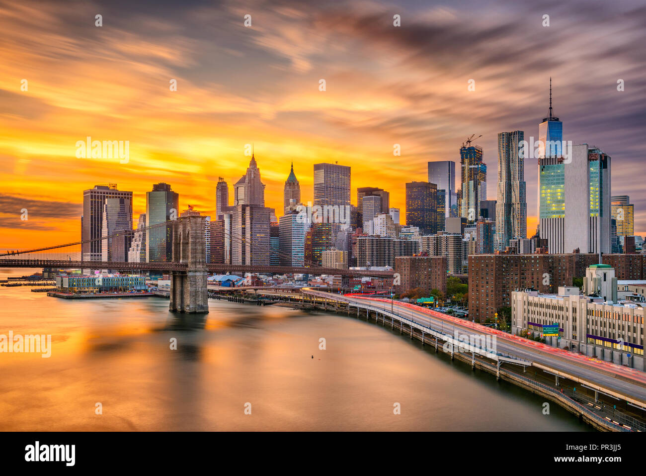 New York, New York, USA Lower Manhattan Skyline über den East River und die Brooklyn Bridge nach Sonnenuntergang. Stockbild