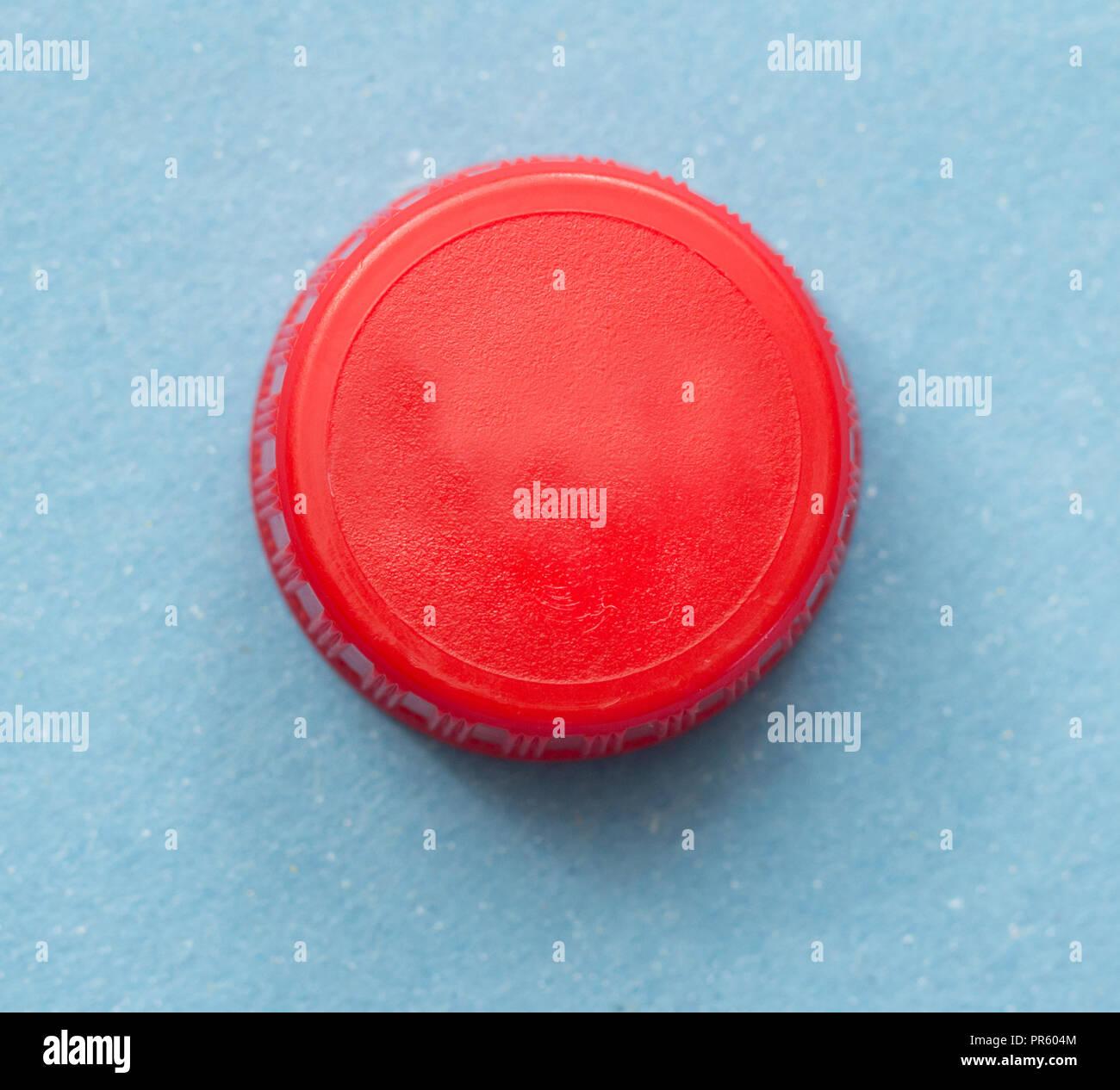 Rote Flaschenverschluss auf blauem Hintergrund Stockbild