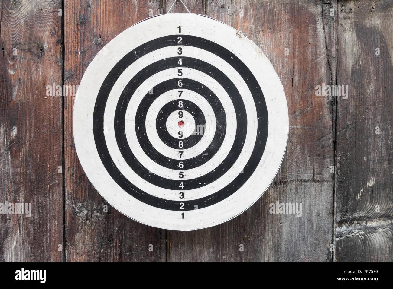 Runde Runde schwarz und weiß Target mit Zahlen hängen an eine Holzwand in der Nähe und im Detail Stockfoto
