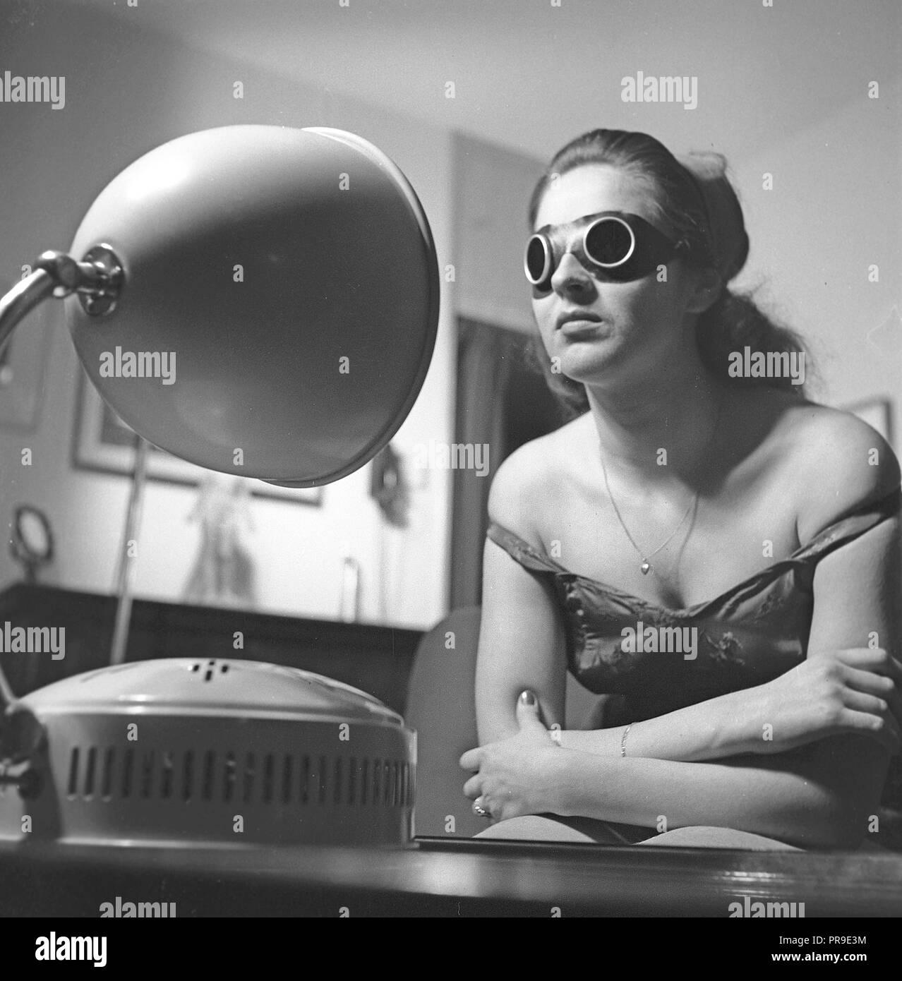 Beauty Care in den 1940er Jahren. Eine junge Frau wird ein Sonnenbad vor der Höhensonne. Das künstliche Sonnenlicht aus dem Hause bräunen Ausrüstungen wie diese höhensonne Bräunen gab und war manchmal zur Behandlung von Krankheiten. Würden Sie schützenden Sonnenbrille zu tragen, als es zu benutzen. Schweden 1940. Foto Kristoffersson Y 81-3 Stockbild