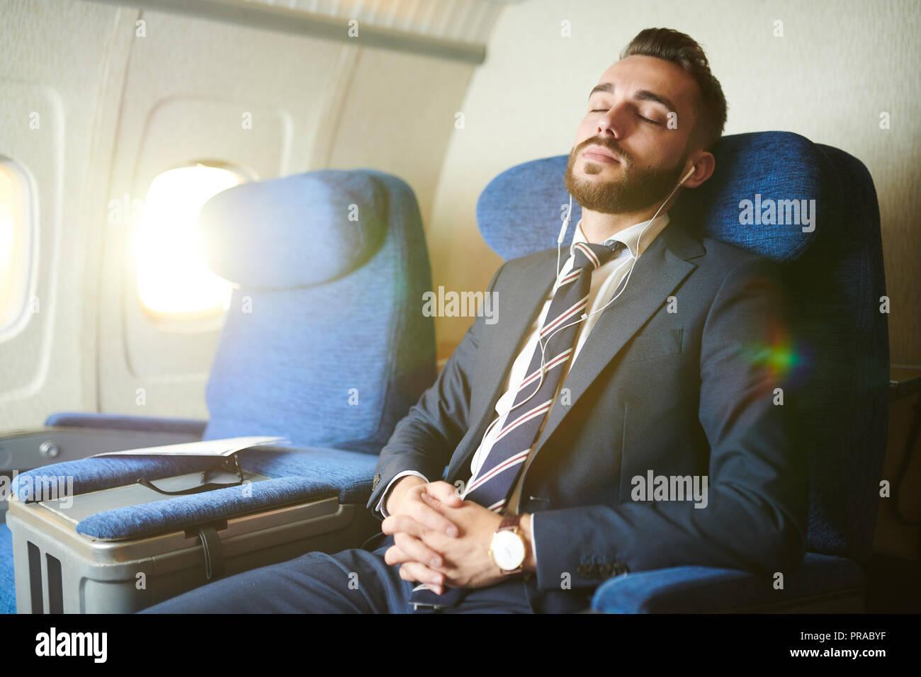 Gut aussehender Geschäftsmann Schlafen im Flugzeug Stockbild