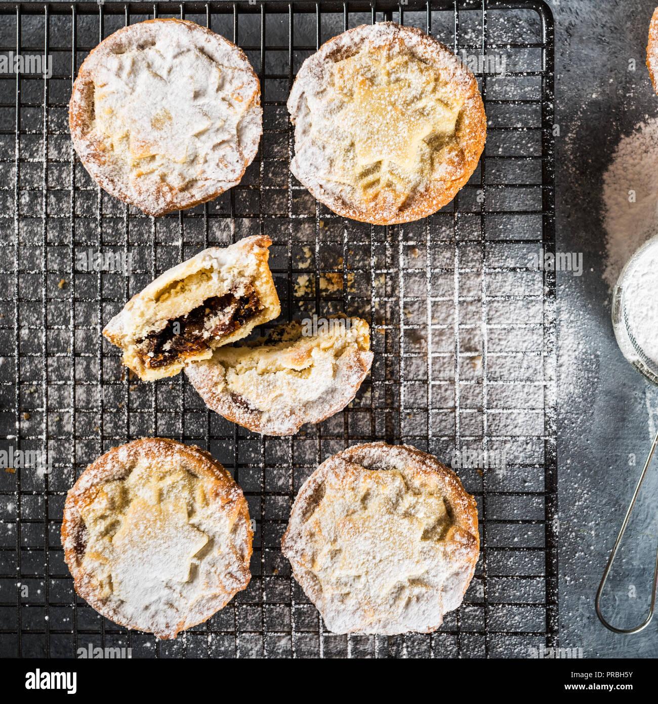 Mince Pies, traditionelle Weihnachten Lebensmittel aus allen Butter mürbteig Gebäck Torten tiefe gefüllt mit pralle Reben Früchte, wie Preiselbeeren, Clementine Stockfoto