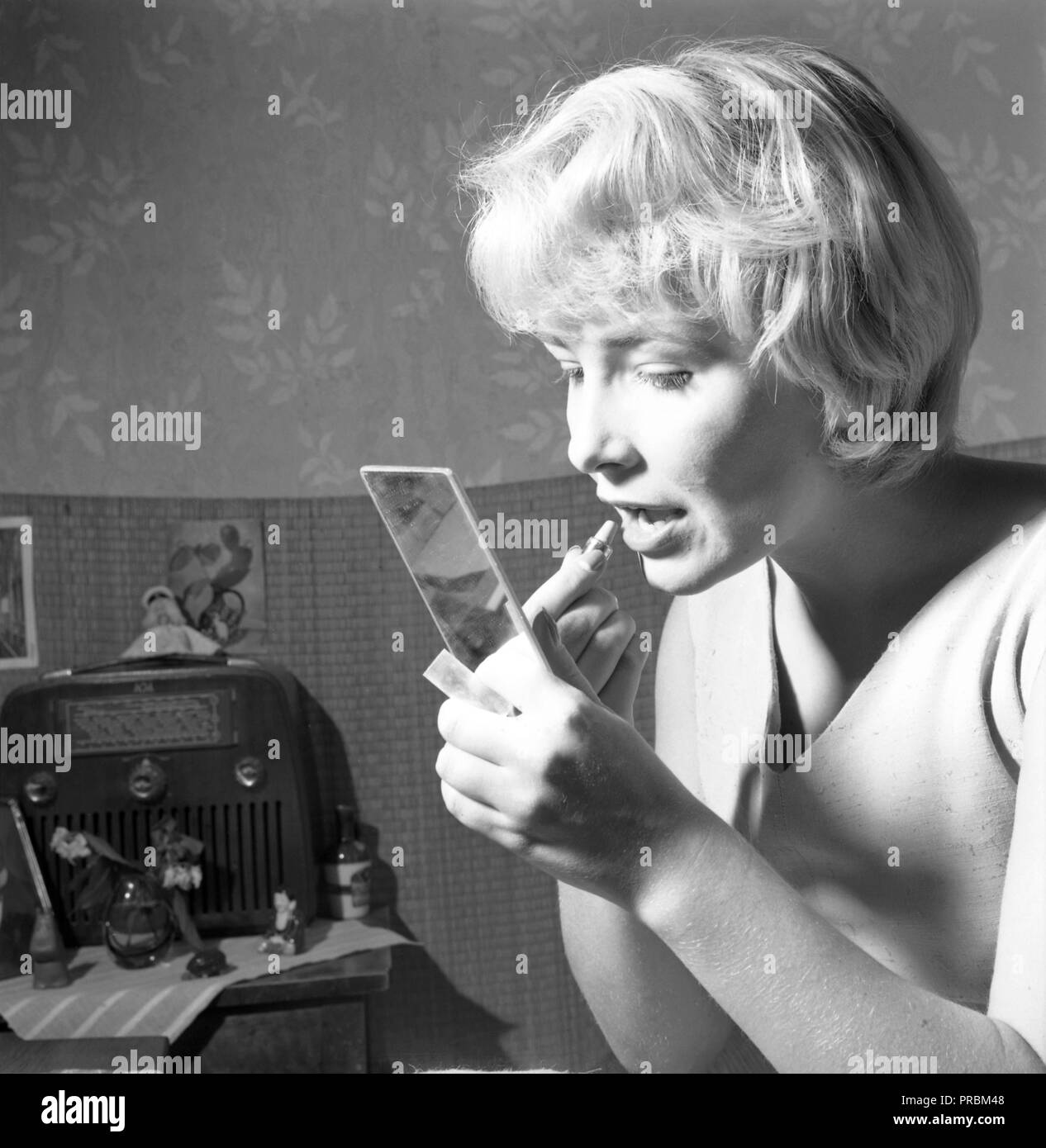 Make-up in den 1950er Jahren. Eine junge Frau hält ein Pocket Mirror Anwendung Lippenstift. Bild Sängerin Lena Granhagen, geboren 1938. Ref 3509 Stockbild