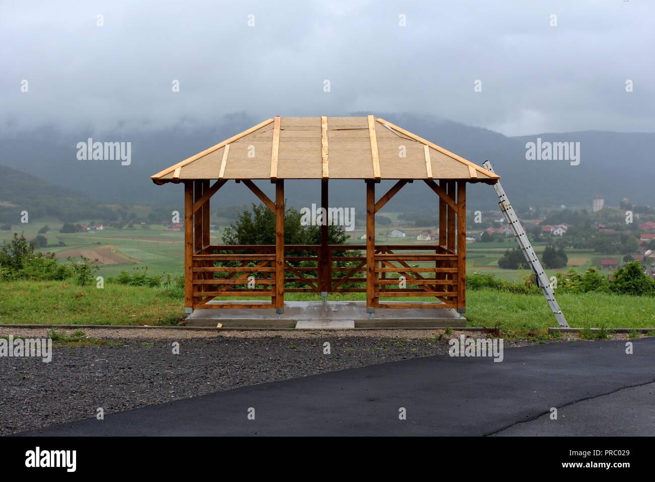 pavillon aus holz montiert auf betonfundament mit dach noch im bau und aluminium leitern neben