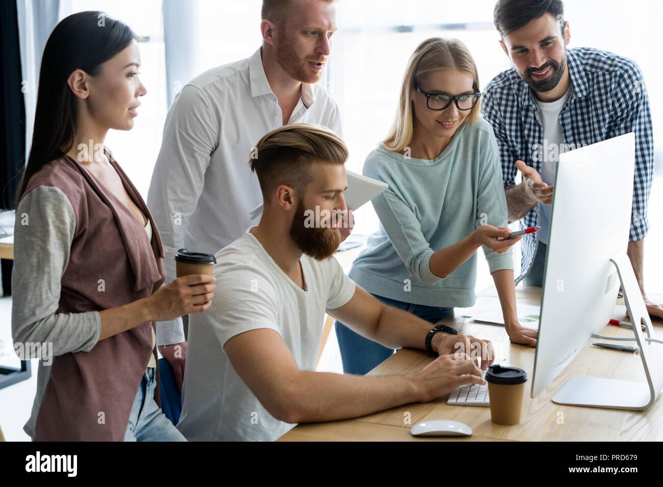 Diskutieren erfolgreiche Projekt. Gruppe von jungen fröhlichen Geschäft Leute arbeiten und kommunizieren, während Sie im Büro Schreibtisch sitzen zusammen mit Kollegen im Hintergrund sitzen. Stockbild