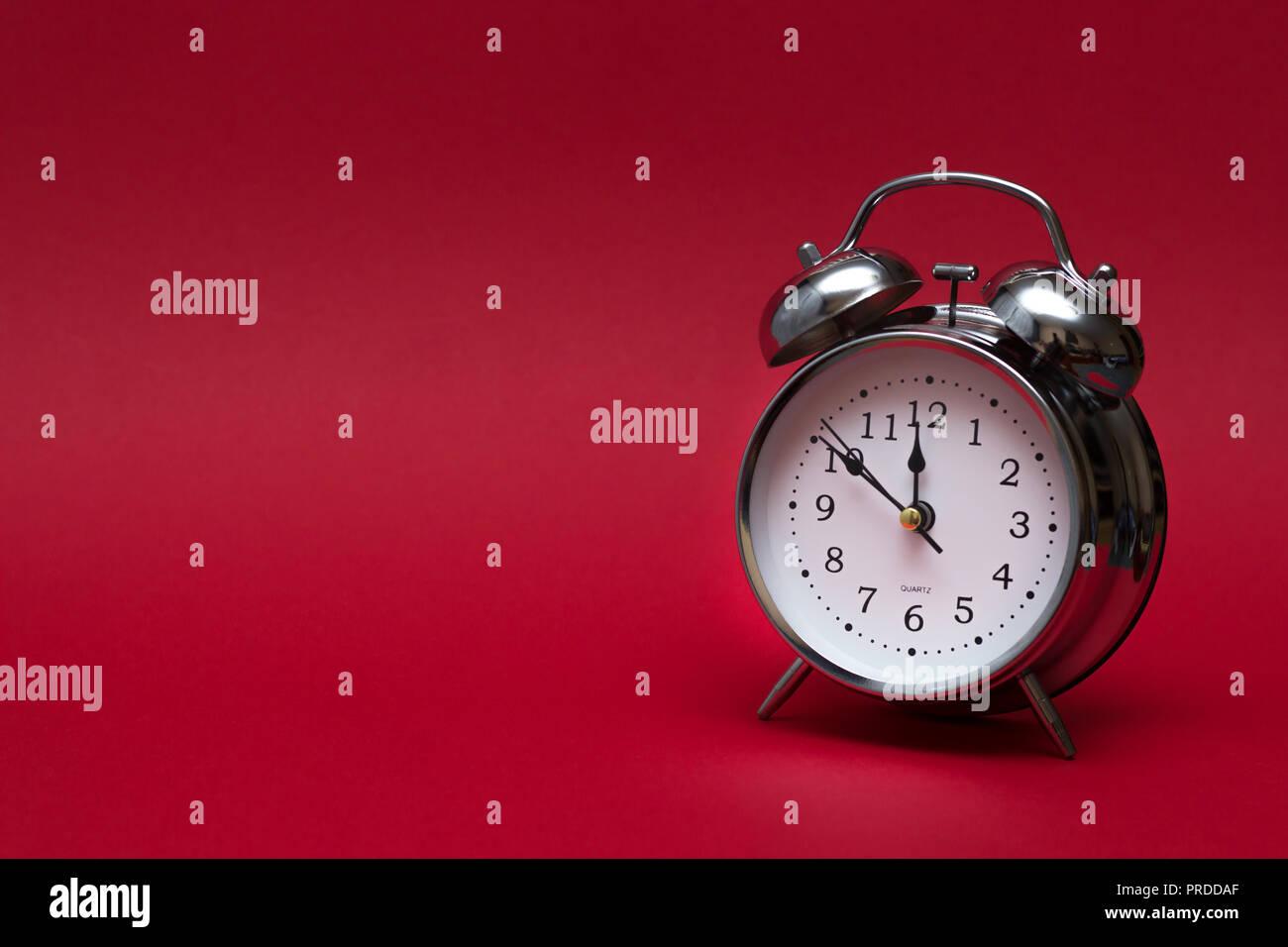 Rot Wecker auf roten Hintergrund. Nahaufnahme. Ansicht von oben. Für zeit Konzept. Stockfoto