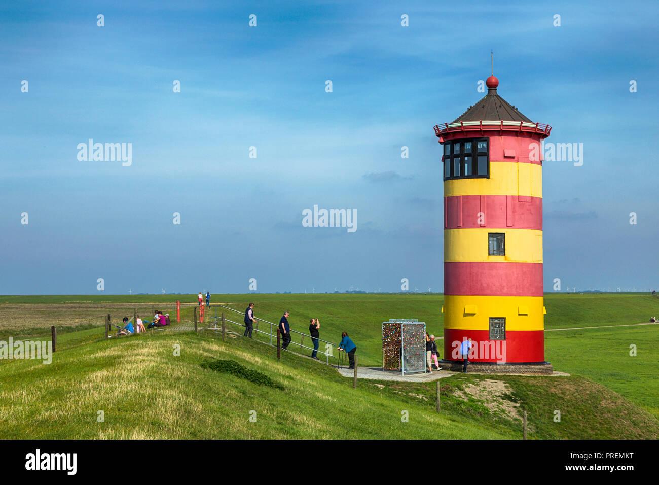 Pilsumer Leuchtturm in Ostfriesland, Touristen gehen, sitzen auf dem Deich und Fotografieren Stockbild
