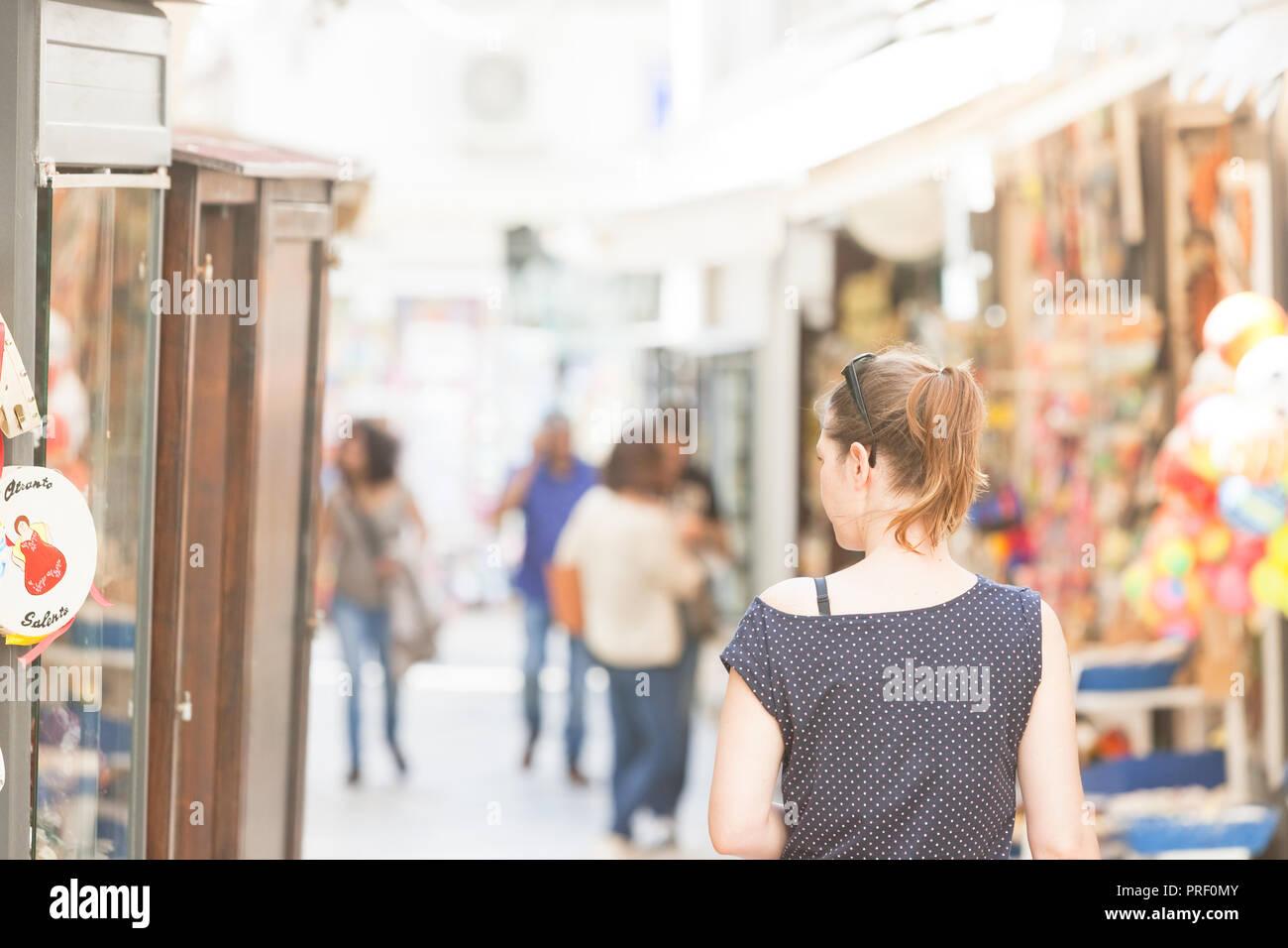 Otranto, Apulien, Italien - eine Frau, die zu Fuß durch die Fußgängerzone von Otranto in Italien Stockfoto