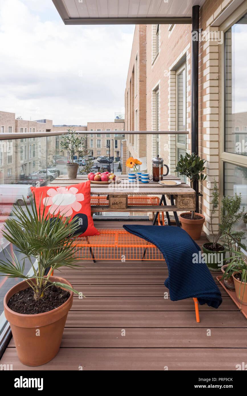 Palette Tisch und Sitzbänke mit hoseplants auf balcont im Norden von London New Build Stockfoto