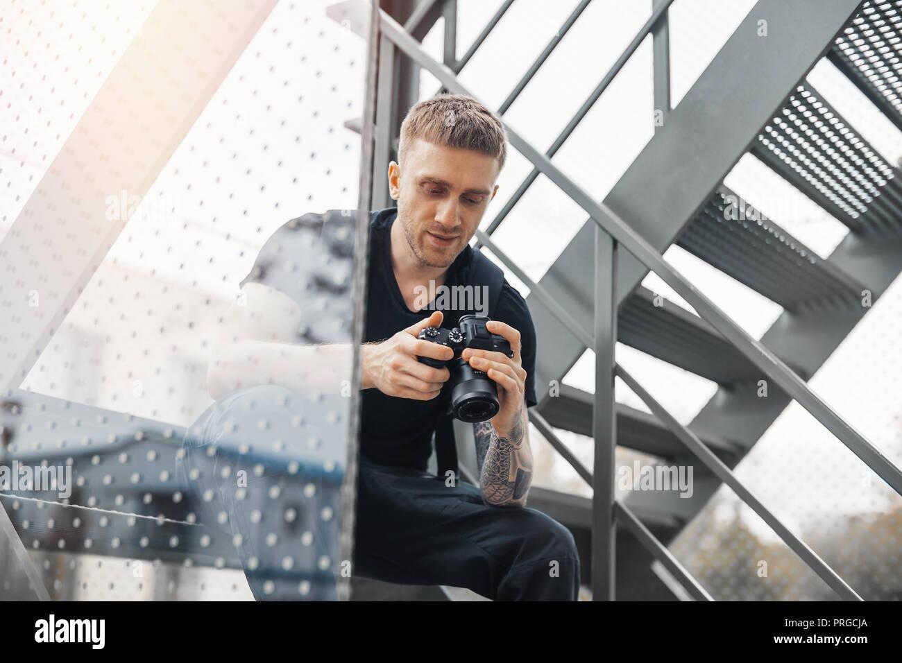 Attraktiver Mann an der Treppe sitzen und Kontrolle der Fotos in der Kamera. Stockbild