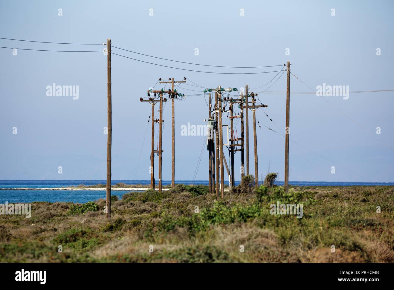 Medium Hochspannungsleitungen in einer ländlichen Gegend in der Nähe von Meer. Stockbild