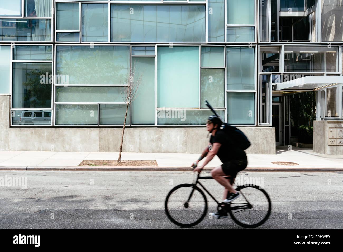 Radfahrer reiten gegen minimalistischen Stil Gebäude in New York. Motion Blur, nicht erkennbar. Stockbild