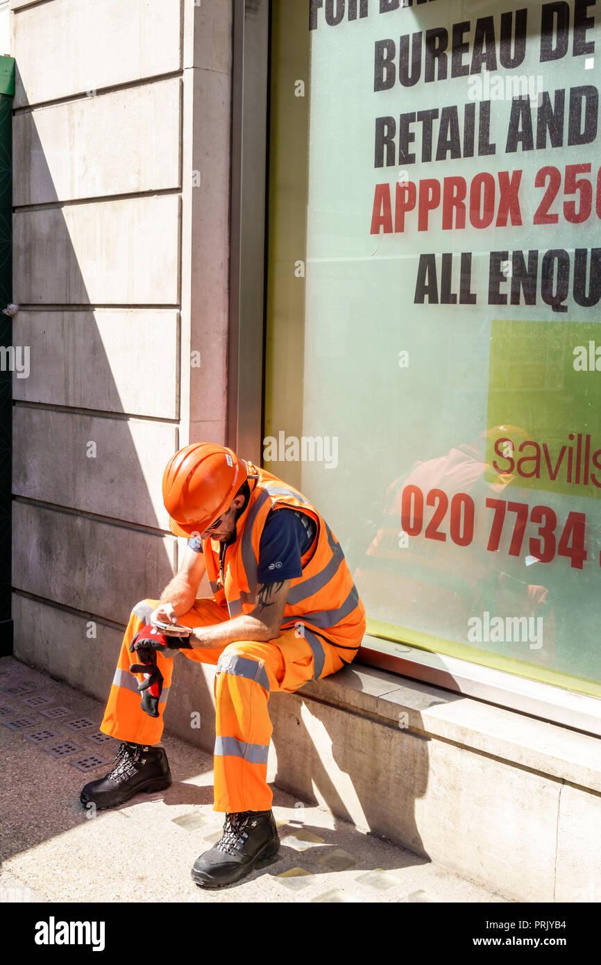 London England Vereinigtes Königreich Großbritannien West End City Westminster Mayfair mann Arbeiter Arbeiter sitzen auf der Fensterbrüstung harten Hut reflektierende Weste pant Stockbild