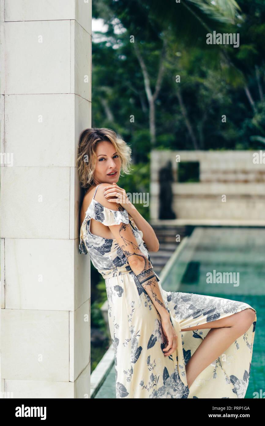 Seitliche Sicht auf attraktive blonde Frau in Kleid Stehen in der Villa mit Swimmingpool auf Hintergrund Stockbild