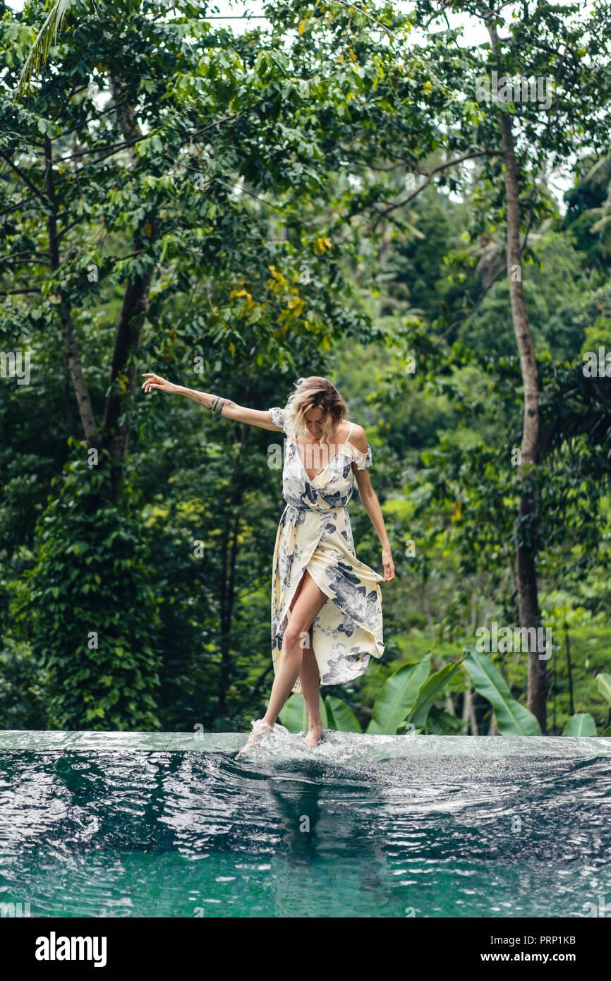 Attraktive blonde Frau im Kleid zu Fuß in der Nähe von Schwimmbad mit grünen Pflanzen auf Hintergrund, Ubud, Bali, Indonesien Stockbild