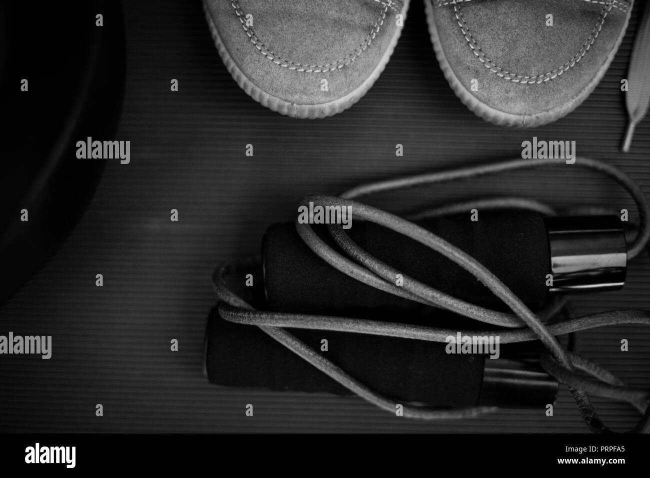 Schwarz-weiß Foto eines Leder Springseil und ein Paar vintage Trainer Stockbild