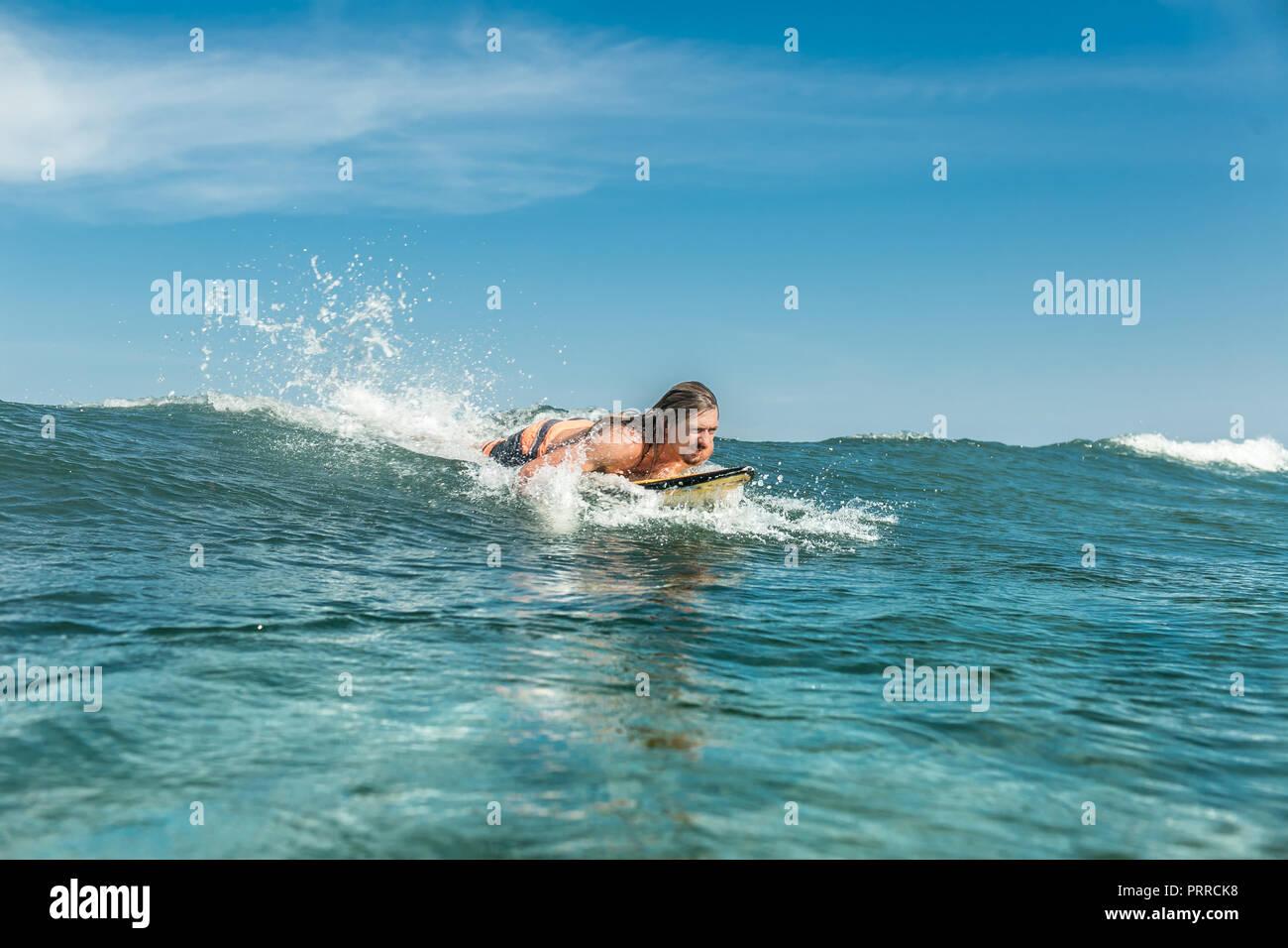Männliche Athleten schwimmen auf Surfen im Meer am Sandstrand von Nusa Dua, Bali, Indonesien Stockfoto