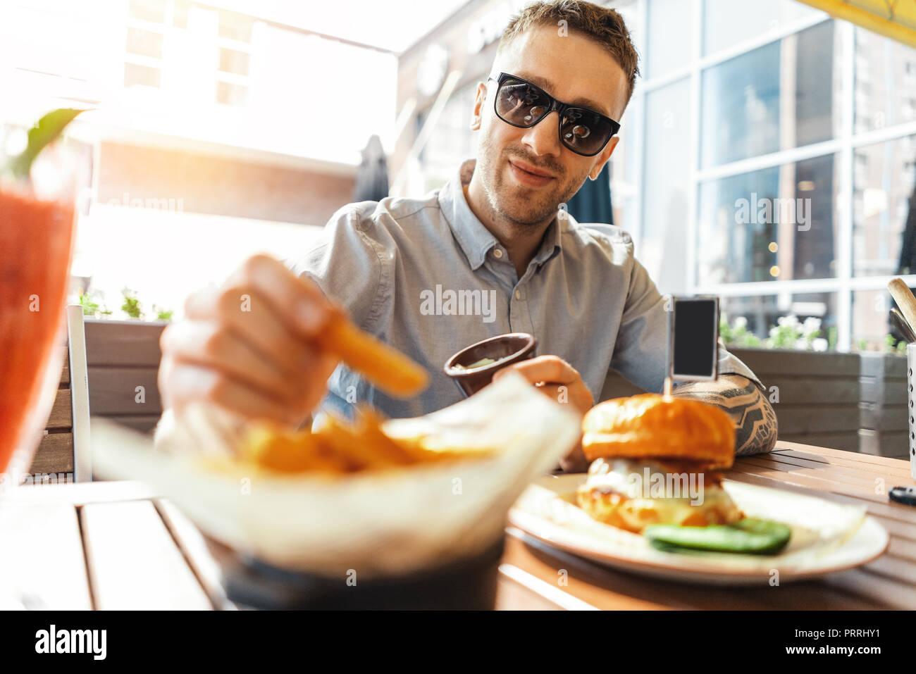 Nahaufnahme von jungen attraktiven Mann essen Pommes und Burger an Street Cafe. Stockbild