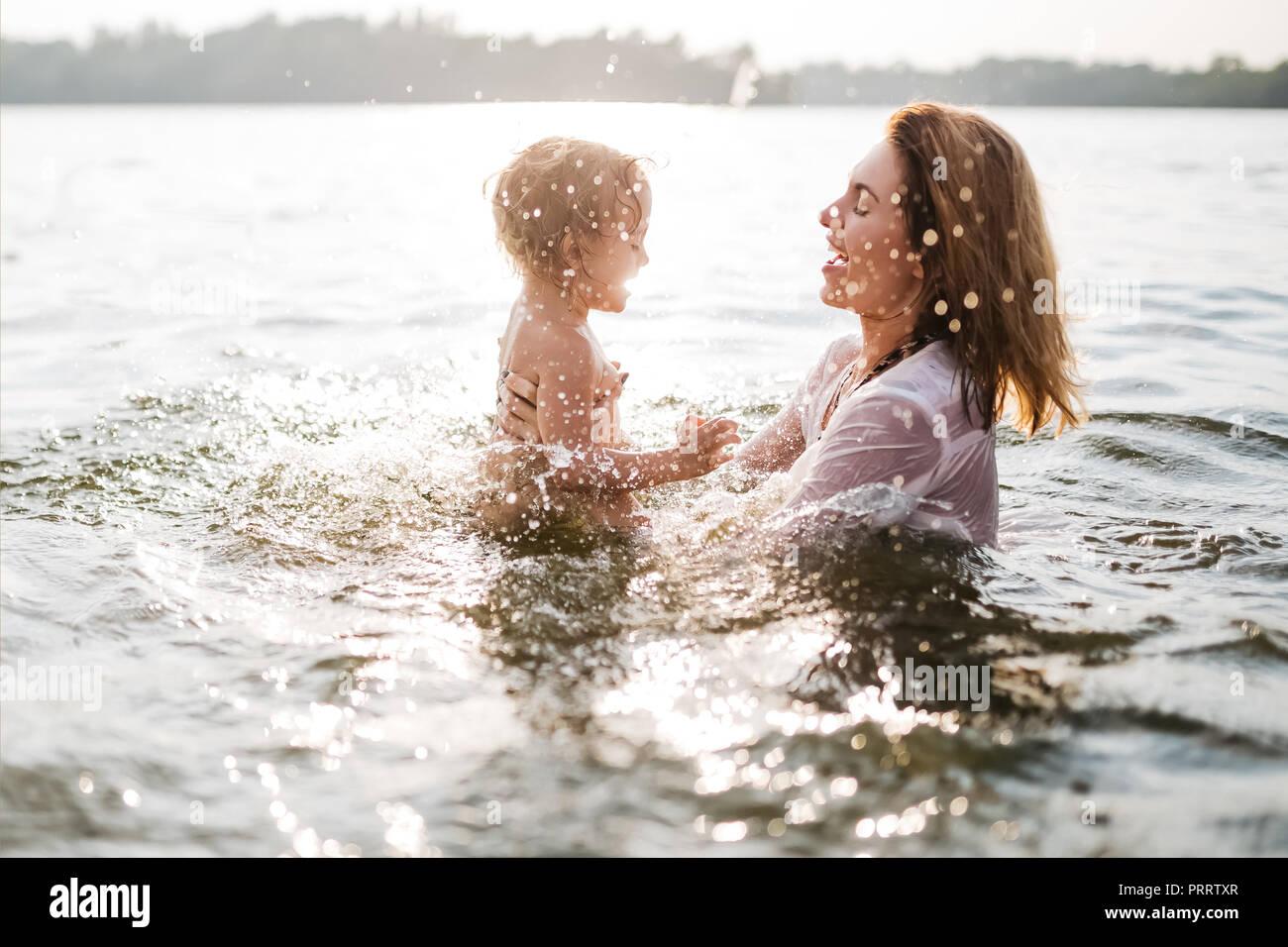 Seitenansicht der glücklichen Mutter und Tochter schwimmen im Fluss Stockbild