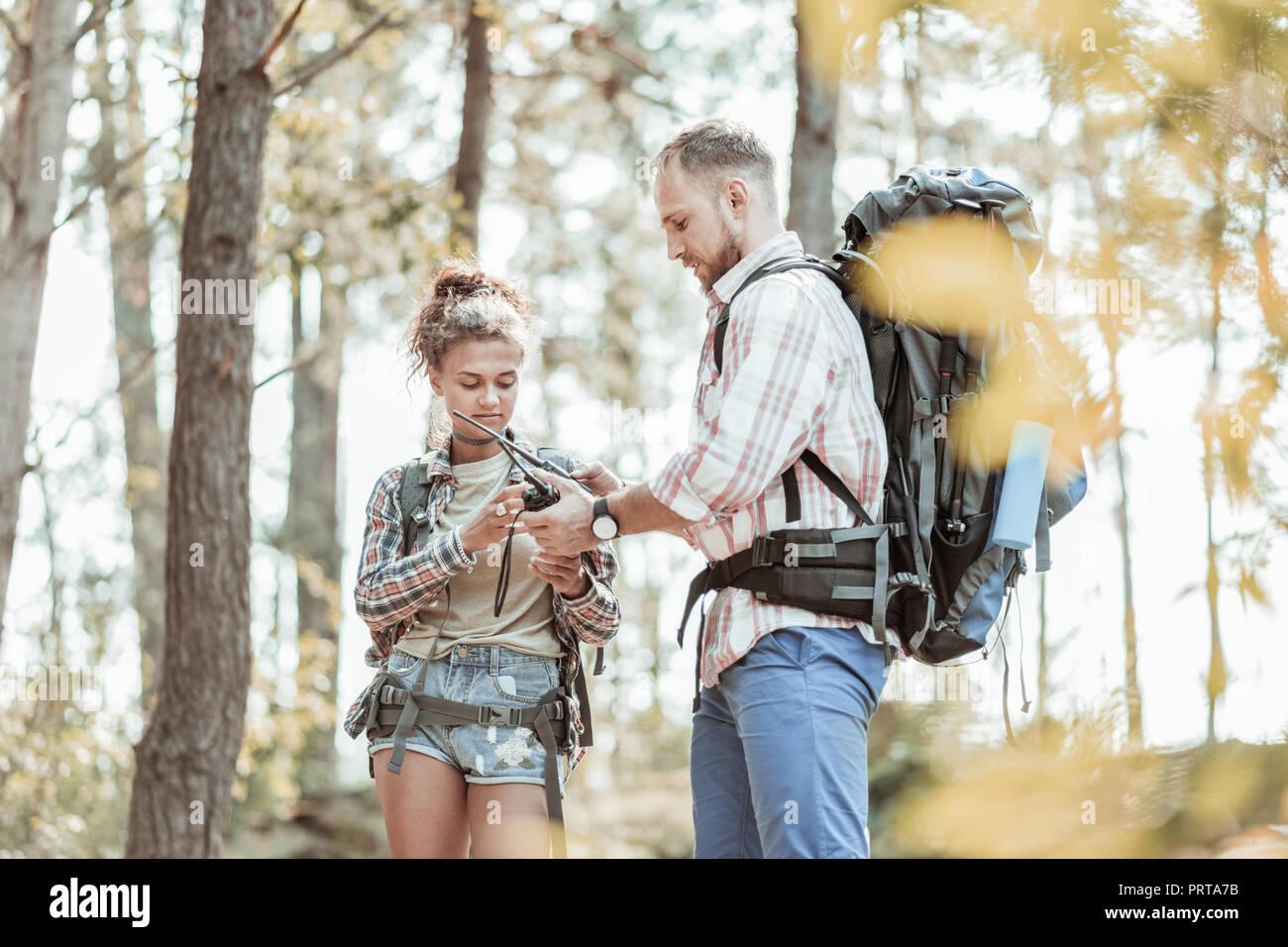 Mann beruhigend seine attraktive Frau, nachdem sie in Wald mit Rucksäcken verloren Stockbild