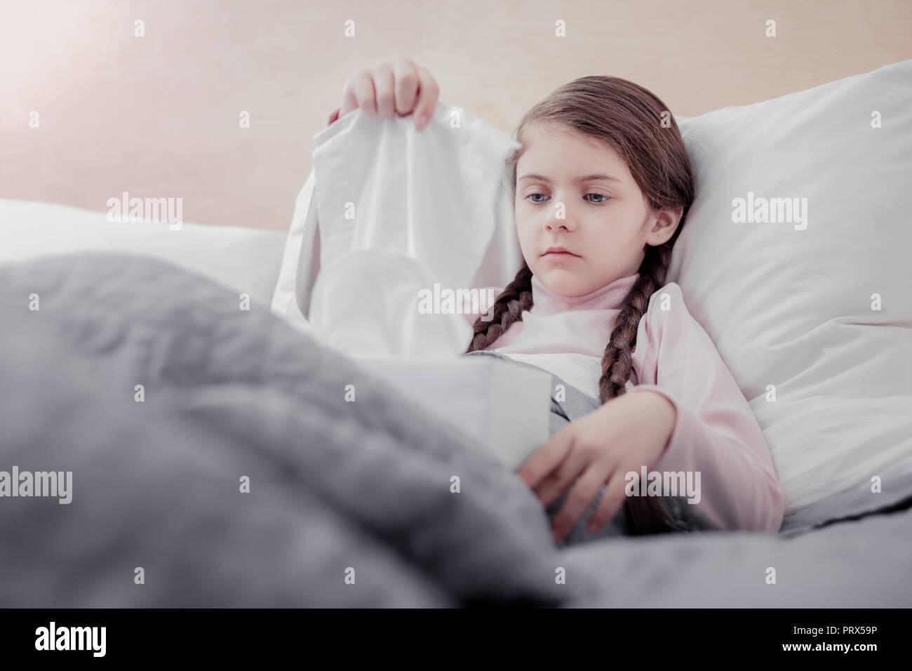 Kleines Mädchen, Servietten, während Sie im Bett Stockbild